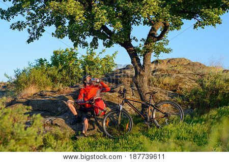 Cyclist in Red Jacket and Helmet Resting and Drinking the Water near Mountain Bike on the Rocky Hill under Beautiful Green Tree. Adventure and Travel Concept.