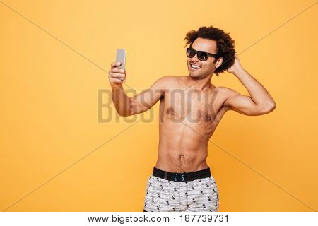 Picture of handsome emotional young african man dressed in shorts standing isolated over yellow background. Looking aside while make selfie by mobile phone.
