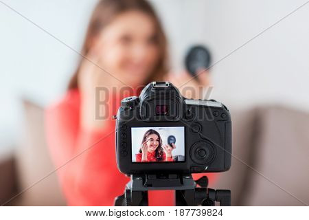 blogging, technology, videoblog, makeup and people concept - happy smiling woman or beauty blogger with eyebrow pencil, mirror and camera recording tutorial video at home
