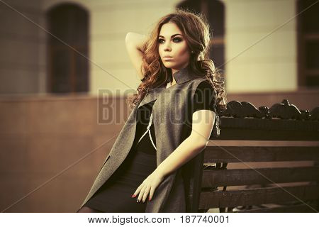 Sad young woman with long curly hairs sitting on bench. Stylish fashion model in sleeveless coat outdoor