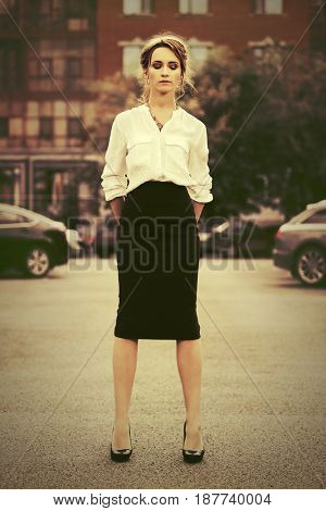 Sad young business woman walking in a city street. Stylish fashion model in white blouse and skirt outdoor