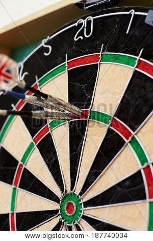 Close Up Of Dartboard With Three Darts In Treble Twenty