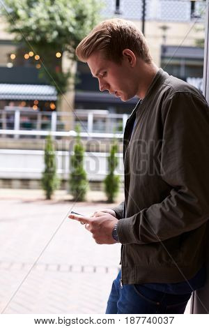 Man Sending Text Message On Mobile Phone In Urban Setting