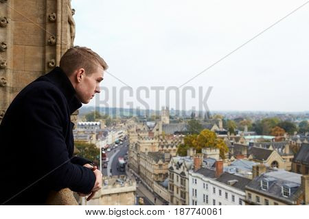 Rear View Of Tourist Looking Out Over View Of Oxford Skyline