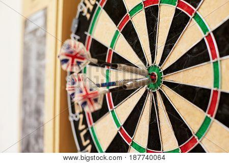 Close Up Of Dartboard With Three Darts In Bullseye