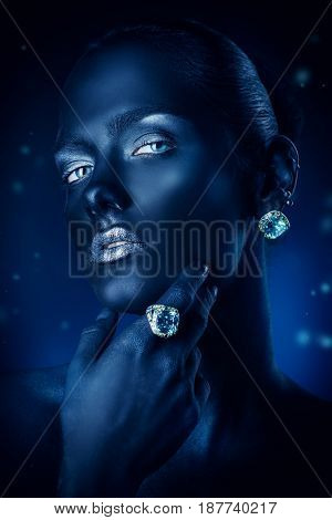 Beauty, fashion portrait. Close-up portrait of a beautiful young woman with black skin, silver glitter lips and beautiful aquamarine ring and earrings. Body painting project. Make-up and jewelry.