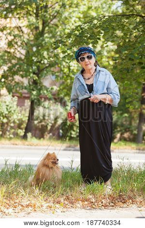Old woman walking around city. Granny female outdoors
