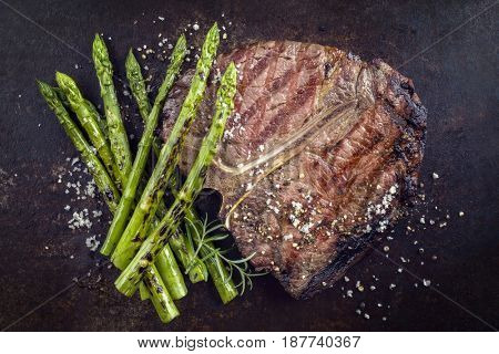 Barbecue dry aged Wagyu Porterhouse Steak with green Asparagus as close-up on an rusty metal sheet