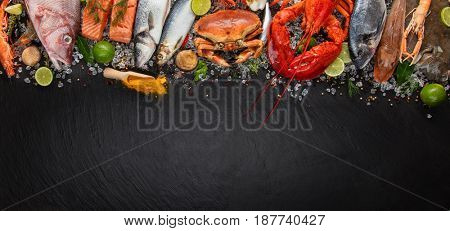 Whole lobster with seafood, crab, mussels, prawns, fish, salmon steak, mackerel and other shells served on black slate stone