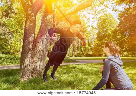 Personal trainer with man at the park fitness training with sling