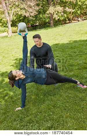 Woman with kettleball in personal fitness training class at the park