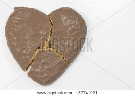 A Broken Heart Shaped Chocolate Cookie, on white background