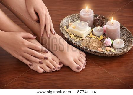 Female feet and hands with brown manicure and spa composition on wooden background