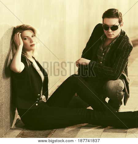 Young couple sitting at the wall in city street. Stylish fashion male and female model outdoor