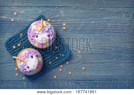 Unicorn cupcakes above blue wooden background