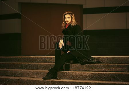 Fashion blond woman sitting on the steps in night city street. Stylish female model in black coat