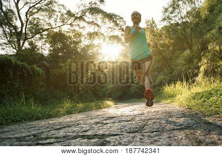 Female athlete running on sunrise forest trail