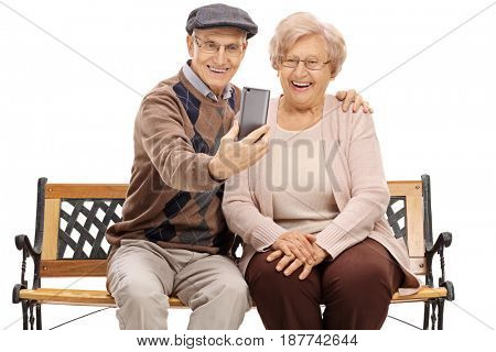 Seniors sitting on a bench and taking a selfie isolated on white background