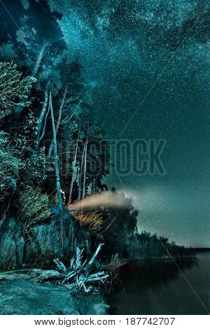 night forest landscape on the bank under a sky with stars and Milky Way