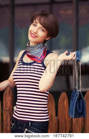 Happy young fashion woman with handbag next to mall in city street. Stylish female model in tank top