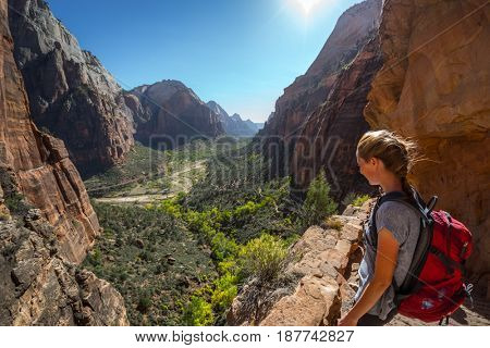 Young woman hiker with backpack stands on the edge and looks down at the valley of Zion National Park, Angels Landing trail, USA