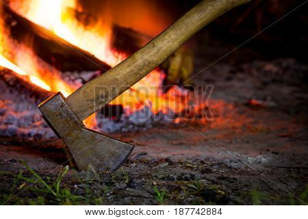 Axe in darkness against hot fire