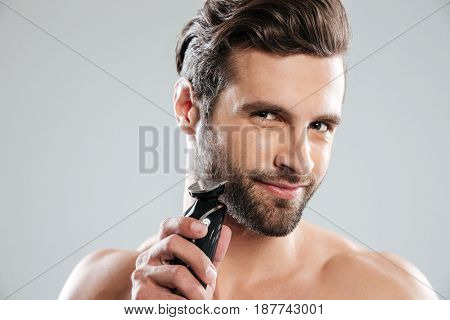 Smiling young man shaving with electric razor and looking at camera isolated over white background