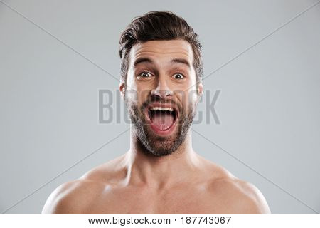 Portrait of an excited bearded man with naked shoulders and open mouth isolated over white background