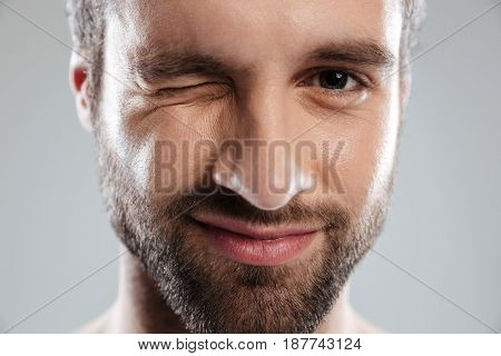 Cropped image of a bearded mans face winking isolated over white background