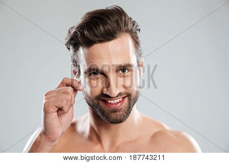 Handsome young man plucking his eyebrows with tweezers isolated over white background