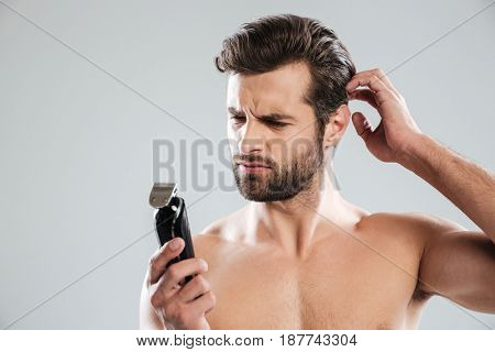Portrait of a pensive bearded guy looking at electric shaver isolated over white background