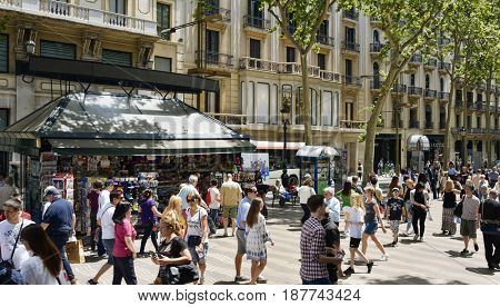 BARCELONA, SPAIN - MAY 22, 2017: People walking by the upper section of La Rambla in Barcelona, Spain. Thousands of people walk daily by this popular pedestrian mall 1.2 kilometer-long