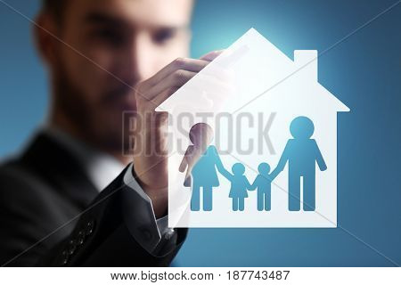 Insurance concept. Businessman drawing family and house, closeup