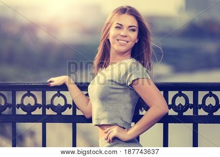 Happy young fashion woman leaning on the cast iron fence. Stylish female model by sunset light