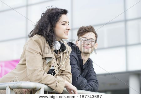 Two smiling teenagers standing leaning on the railing and talk