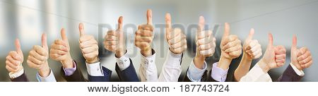 Many business people hands holding thumbs up as teamwork concept