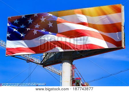 Large billboard with the USA american flag with blue sky behind it.