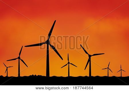 Many windmills as silhouette with orange sky sunset