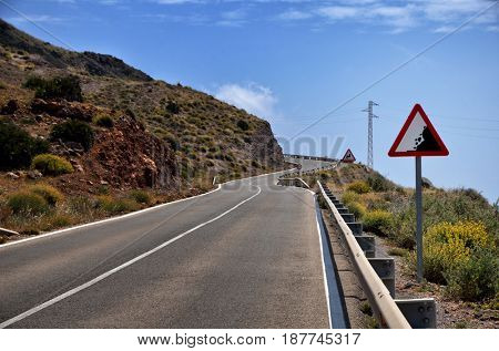 Warning sign in a red triangle on a mountain road
