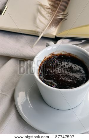 A cup of coffee on a background of notepad with a feather