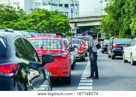 Bangkok Thailand May 19th 2017; A man who selling flower garland to a taxi on the Pradidmanutham road to Pradidmanutham intersection Bangkok Thailand when the cars are stopped for red light traffic