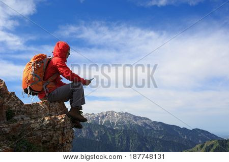 young woman backpacker using digital tablet on mountain top