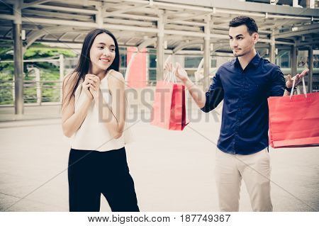 happy young couple with shopping bags walking in mall