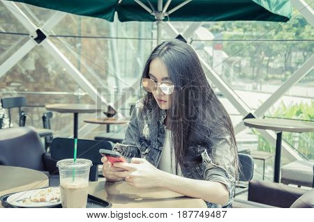 The girl is playing mobile in a cafe.