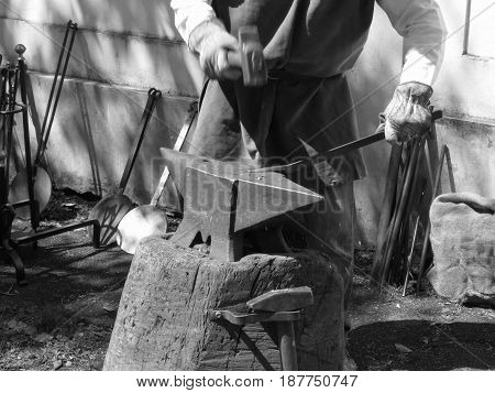 Blacksmith manually forging the molten metal with hammer on the anvil . Black and white photo . Photo taken during outdoor public event (no ticket required) in public place . Pistoia Italy