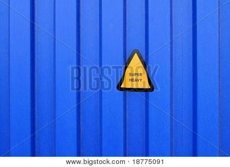Blue sidewall of a cargo container with a super heavy sign