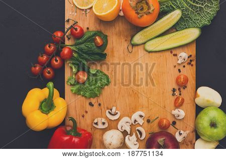 Cooking healthy vegetarian food background. Frame of fresh organic vegetables on black with copy space. Natural food and wooden cutting board