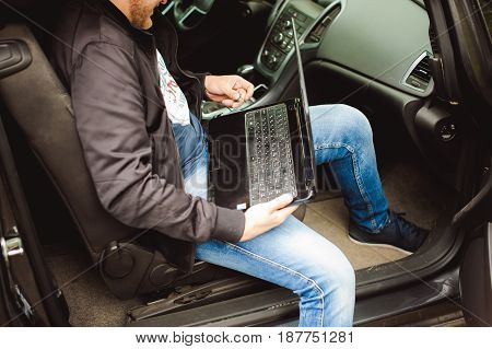 Professional Man With A Laptop In Car Tunes Tuning Control System, Updating Software, Gaining Access