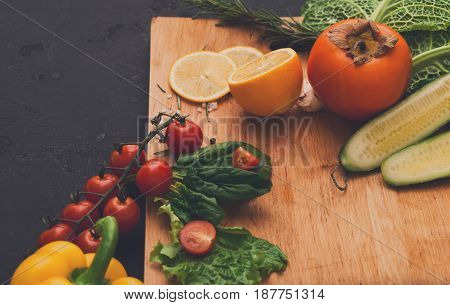 Cooking healthy vegetarian food background. Frame of fresh organic vegetables on black. Natural food and wooden cutting board with copy space.