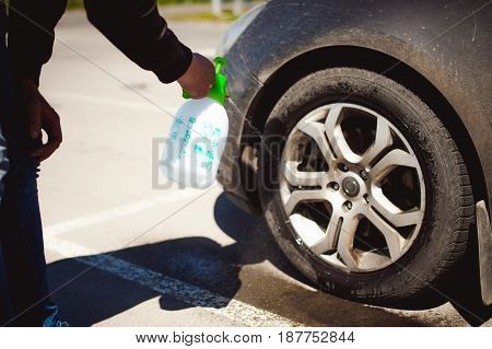 Young Bearded Man Washes His Car's Wheel Rims, Spraying Water From Spray, In Street Parking